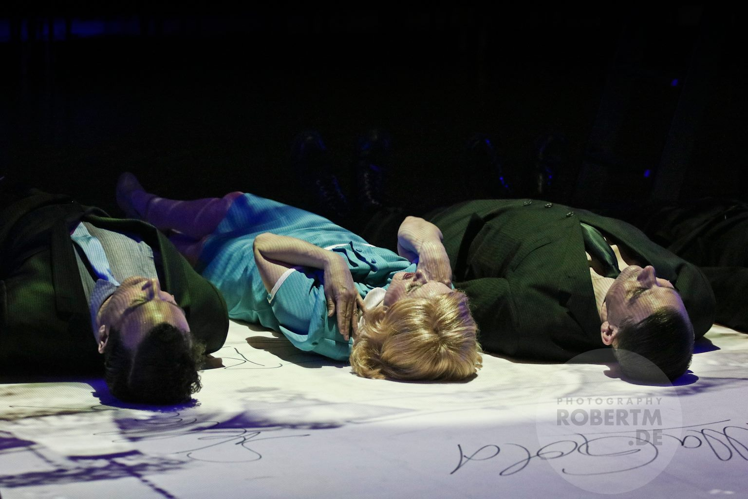 "The soloists of ""Stella"" lying on the floor, looking at the camera above, which creates the film images projected onto the glass pavillion. (Photo: Robert M)"