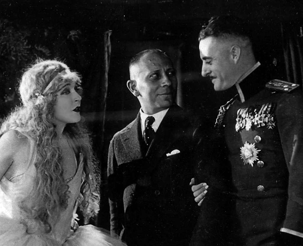 "Erich von Stroheim with his two stars, Mae Murray and John Gilbert, shotting ""The Merry Widow,"" 1925. Miss Murray is seen here in her ""showgirl"" costume."" (Photo: Archive Operetta Research Center)"