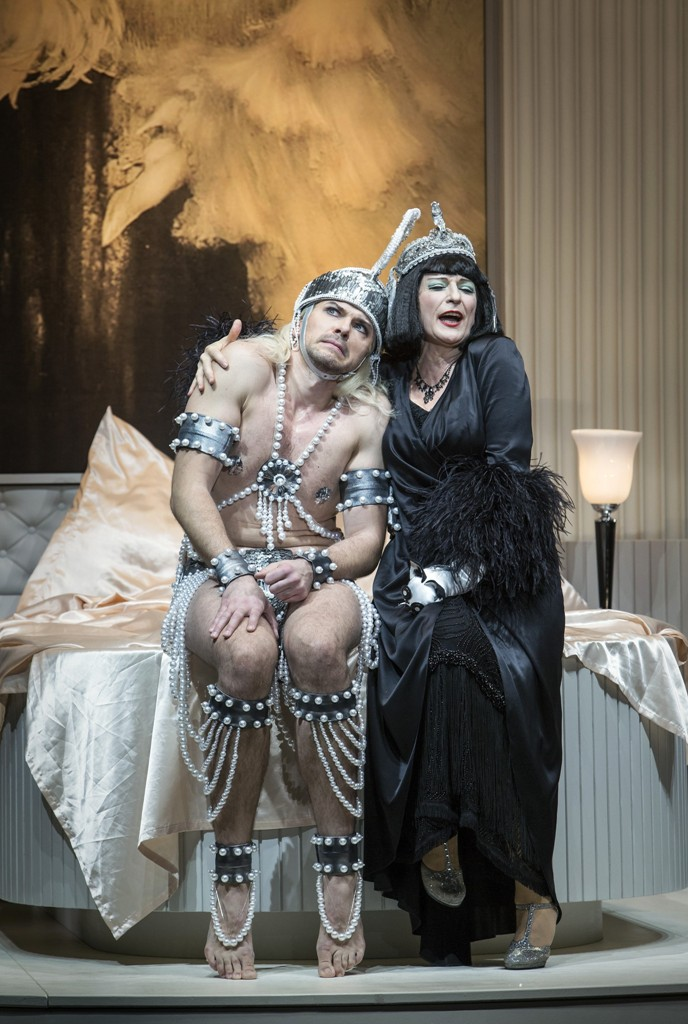 "Dominik Köninger as Silvius, being bedded by Dagmar Manzel in ""Die Perlen der Cleopatra"" at the Komische Oper Berlin. (Photo: Iko Freese/drama-berlin.de)"