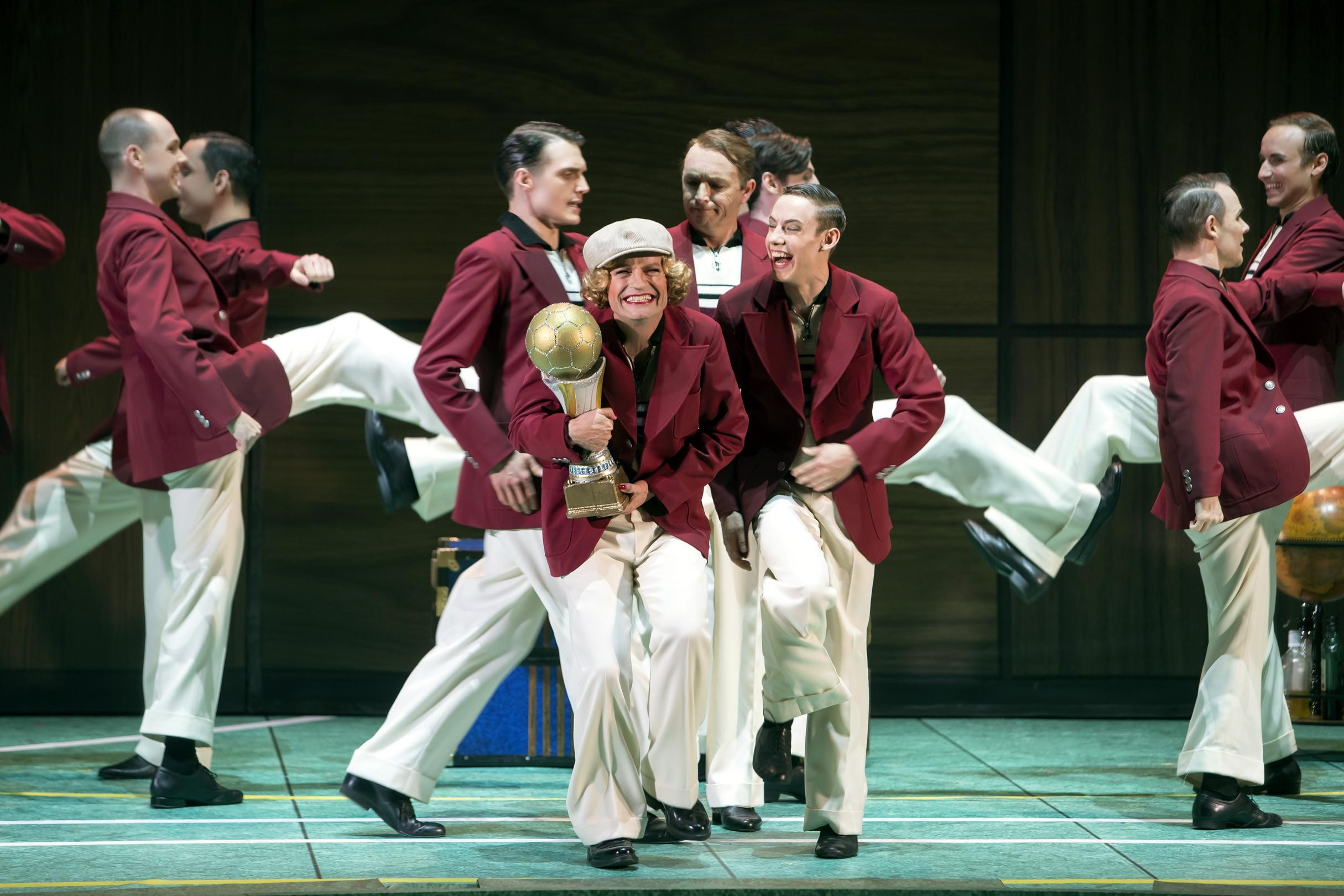 "Christoph Marti as Roxy (in football uniform) and the football team, including Jörn-Felix Alt, in ""Roxy und ihr Wunderteam"" at Komische Oper Berlin. (Photo: Iko Freese / drama-berlin.de)"
