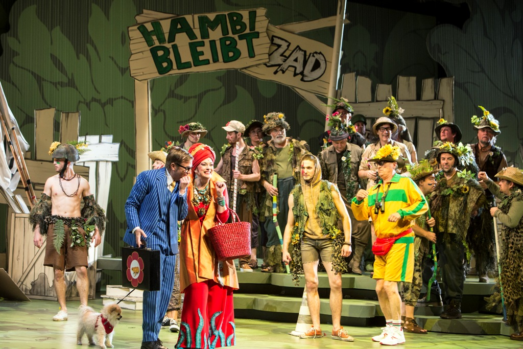 "The 2019 production of Offenbach's ""Großherzogin von Gerolstein"" at Oper Köln, with Jennifer Larmore in the tile role (middle left) and Miljenko Turk (Baron Puck, left), Vincent Le Texier (General Boum, far right), plus dancers and chorus. (Photo: Bernd Uhlig)"