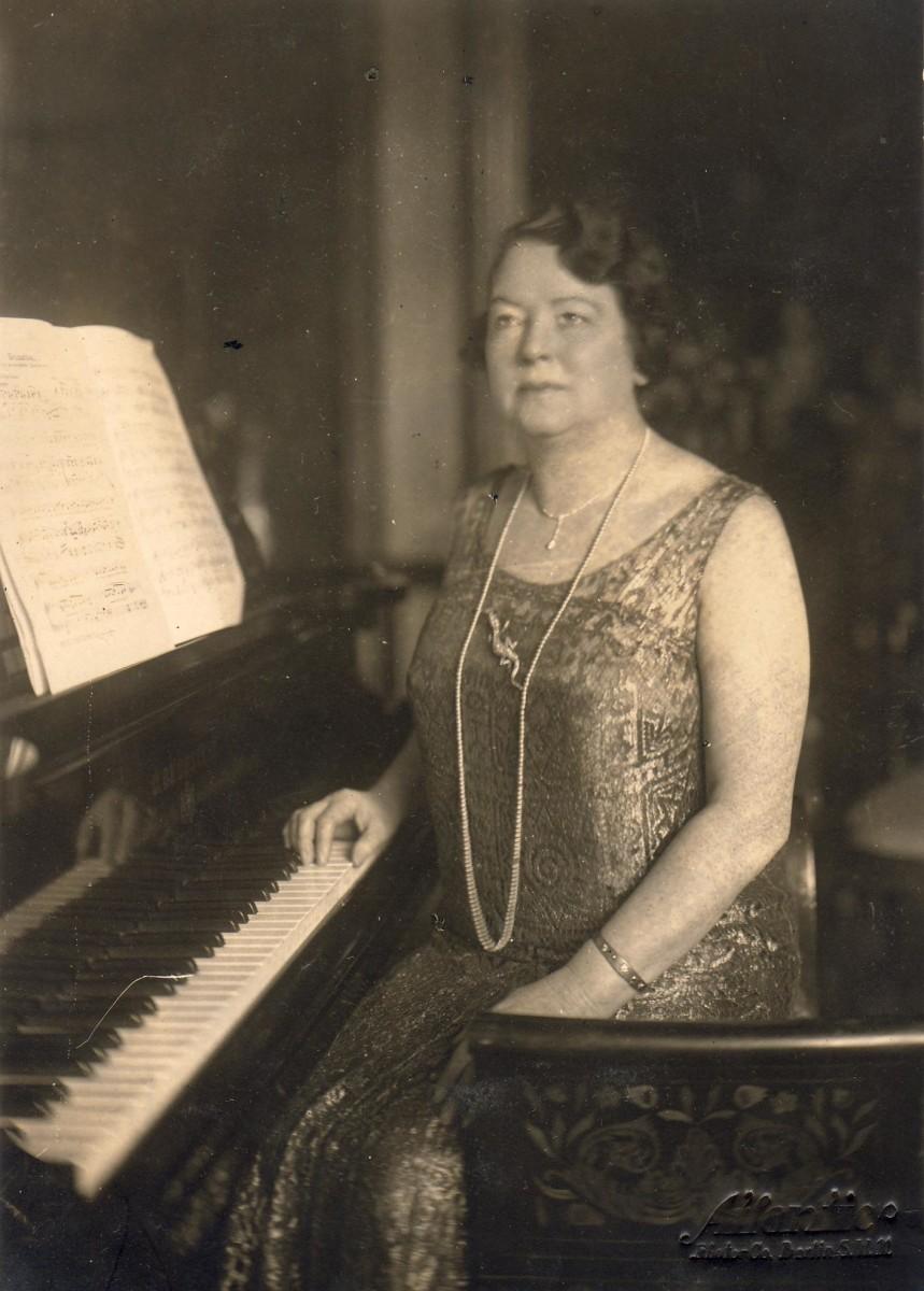 Carita von Horst, née Partello, sitting at the piano.