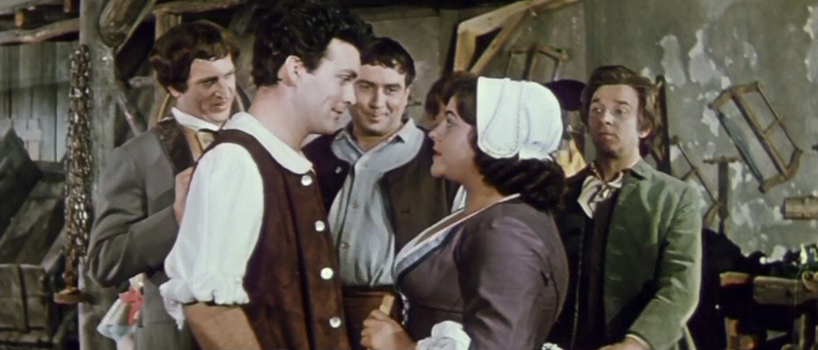 Campistrel (l.) and Marceline in her beautiful laundrette, with the blue collar friends and admirers of Lurette. (Photo: Screenshot from the DEFA film version)
