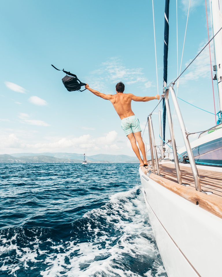 A young man returning to harbor on his boat. (Photo: Oliver Sjostrom / Unsplash)