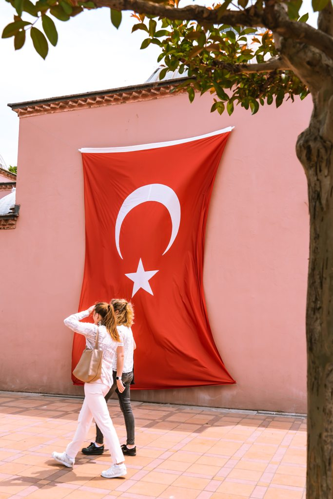 Young woman walking past a Turkish flag. (Photo: Jean Carlo Emer / Unsplash)