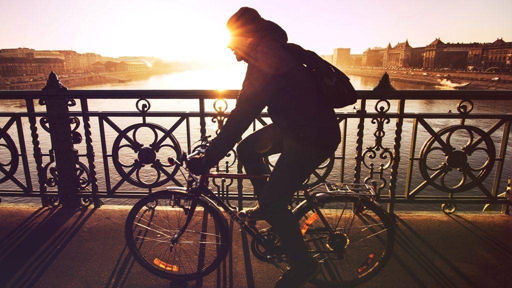 A man cycling across a bridge in Budapest. (Photo: Viktor Keri / Unsplash)