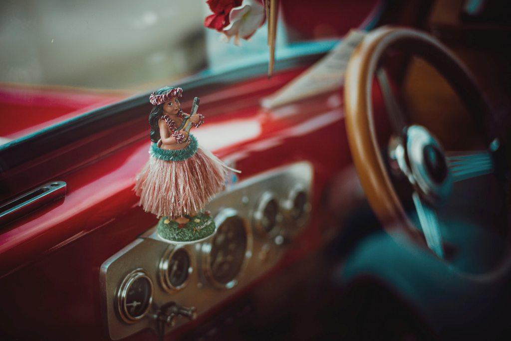 A Hawaiian hula dancer as a doll in a car. (Photo: Aleks Marinkovic / Unsplash)
