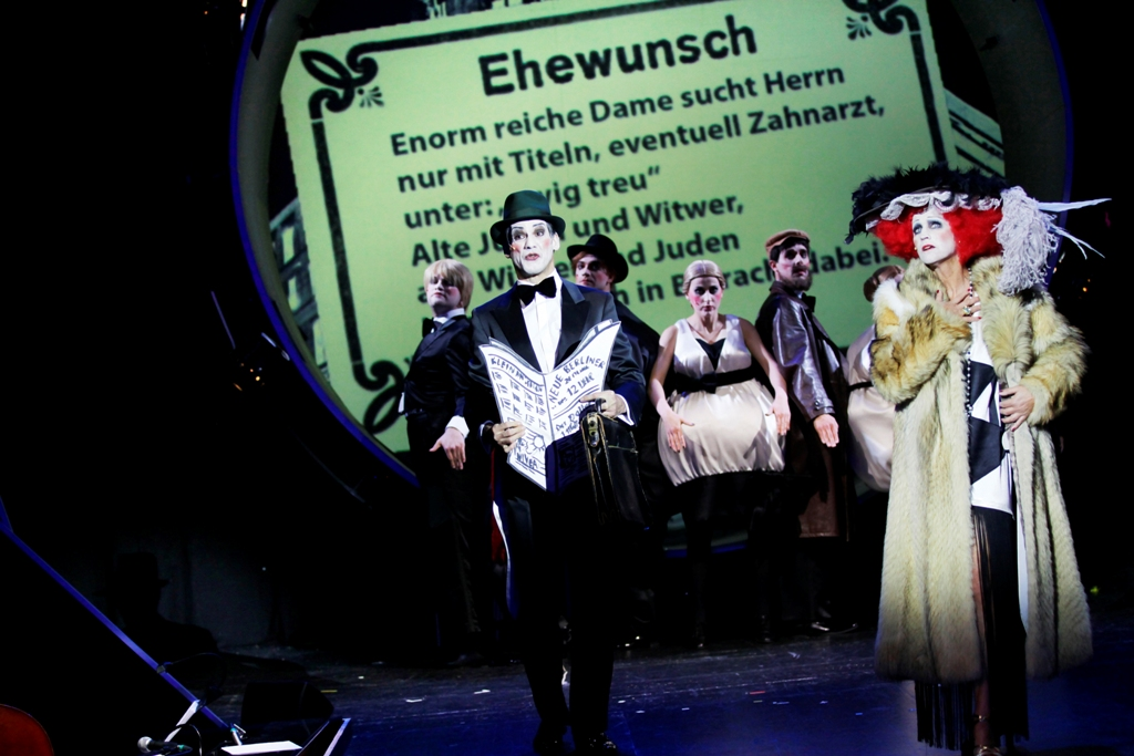 """Mehmet Yılmaz (l.), Catherine Stoyan and ensemble in """"Alles Schwindel,"""" reading out contact ads. (Photo: Ute Langkafel / Gorki Theater)"""