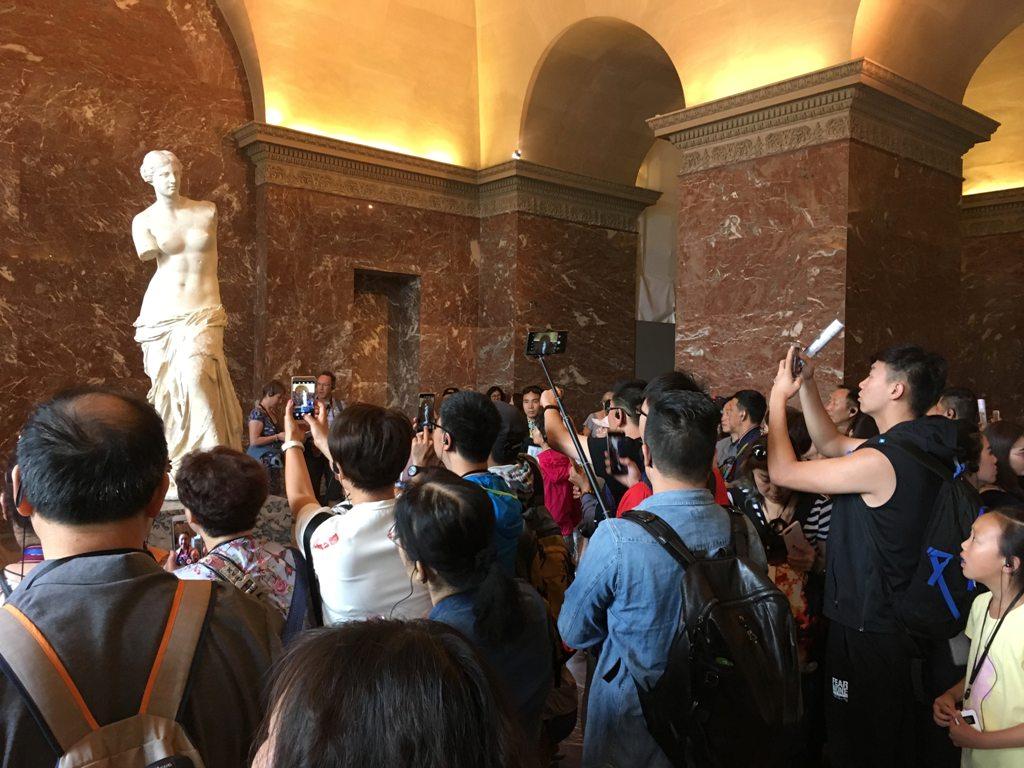 The Venus de Milo in Paris, surrounded by tourists. (Photo: Miquel Rossy / Unsplash)