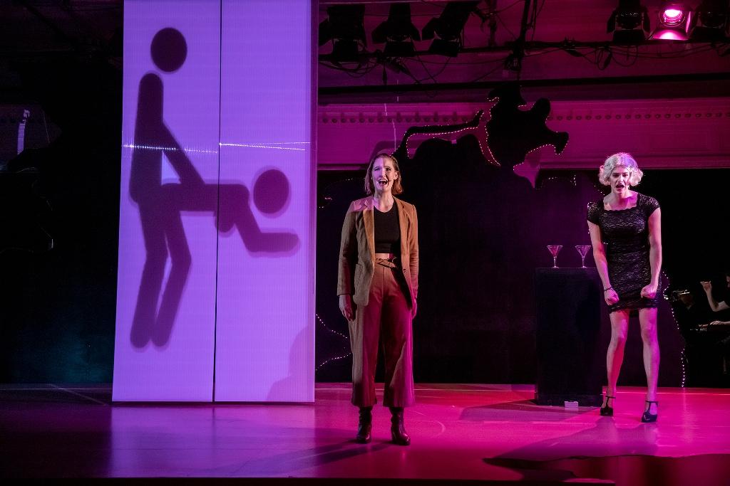"""Der Moment der Enthüllung: Veronika de Vries als Regula Hartmann-Hagenbeck (l.) und Joel Zupan als Alina Deutschmann in """"Eine Stimme für Deutschland"""". (Foto: MIZAFO / Neuköllner Oper)"""