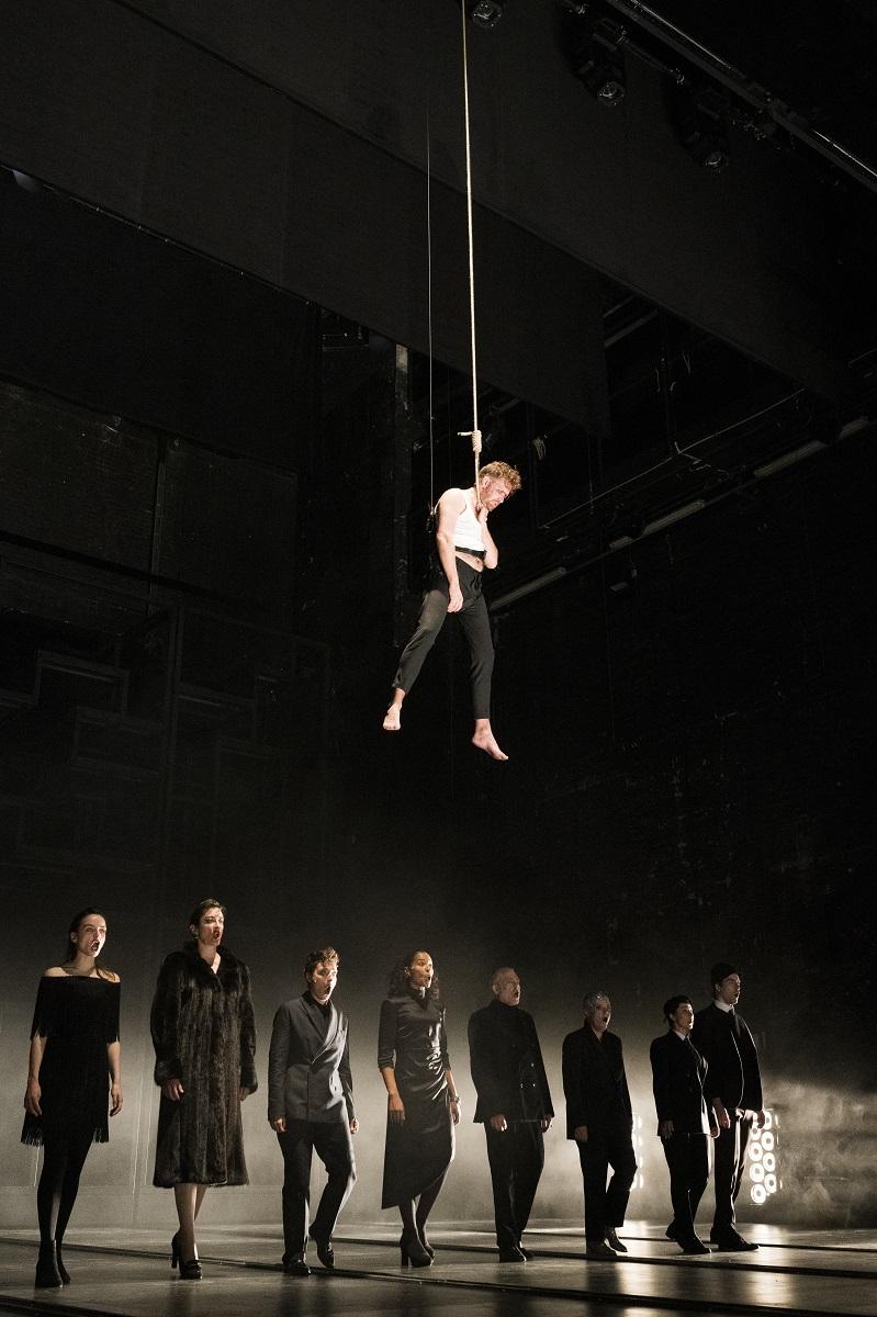 """Nico Holonics hanging on a rope, Laura Balzer, Constanze Becker, Kathrin Wehlisch, Cynthia Micas, Tilo Nest, Josefin Platt, Julia Berger, and Nicky Wuchinger in """"Dreigroschenoper."""" (Photo: Jörg Brüggemann / OSTKREUZ)"""